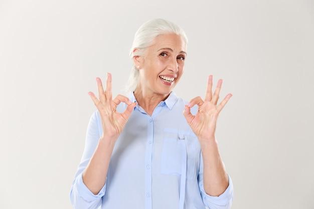 Retrato de mujer senior sonriente en camisa azul mostrando gesto ok
