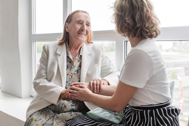 Retrato de mujer senior sosteniendo la mano de su nieta mientras está sentada en el alféizar de la ventana