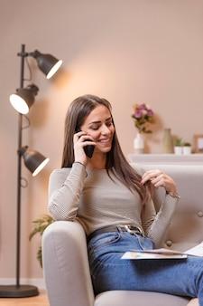 Retrato de mujer sentada en el sofá y hablando por teléfono