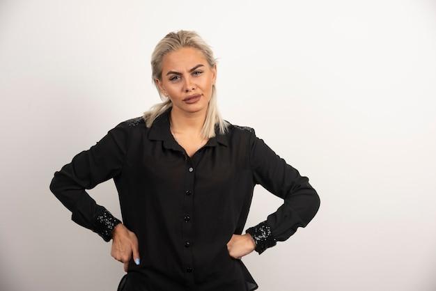 Retrato de mujer seria en camisa negra posando sobre fondo blanco. foto de alta calidad