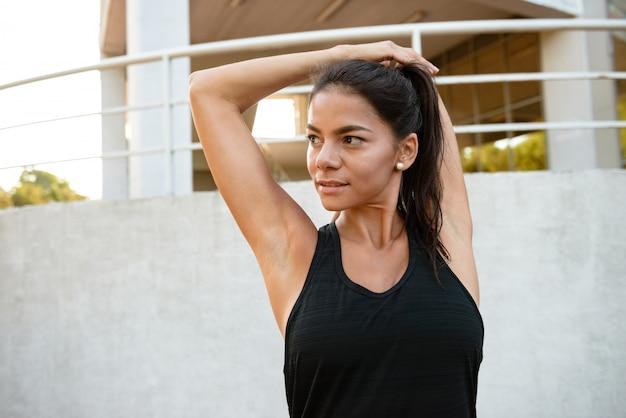 Retrato de una mujer seria fitness estirando sus manos