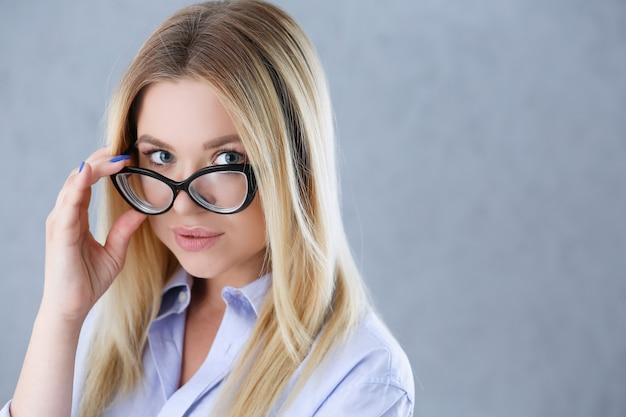 Retrato de una mujer sexy en la camisa de un hombre con gafas