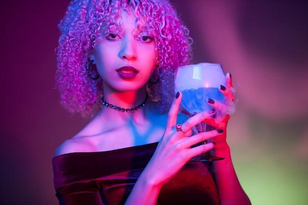 Retrato de una mujer sexy y misteriosa bebiendo una bebida alcohólica