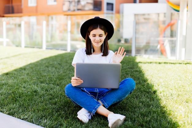 Retrato de mujer sociable sentada en la hierba verde en el parque con las piernas cruzadas durante el día de verano mientras usa una computadora portátil y un auricular inalámbrico para video llamada