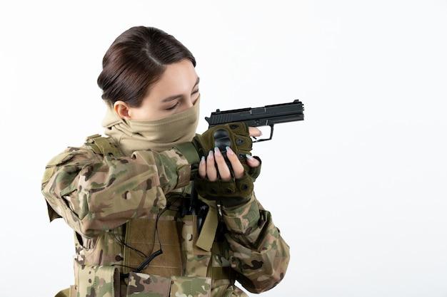 Retrato de mujer soldado con pistola en pared blanca de camuflaje