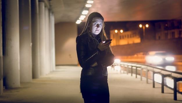 Retrato de mujer solitaria escribiendo un mensaje de texto en la calle oscura