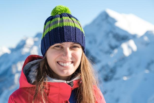 Retrato de una mujer con un sombrero de invierno con un pompón sobre un paisaje de montaña invernal