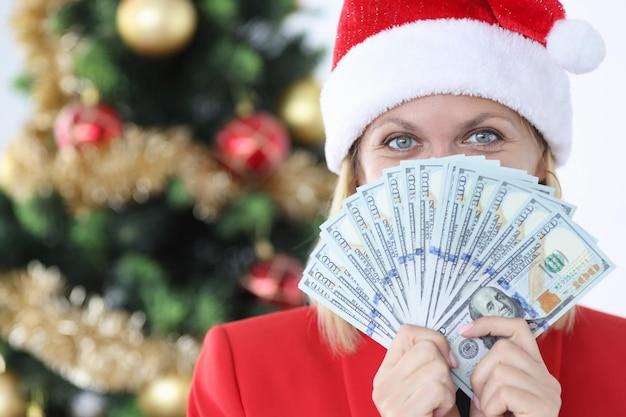 Retrato de mujer con sombrero de santa claus sosteniendo ventilador con efectivo dólares americanos navidad y nuevo