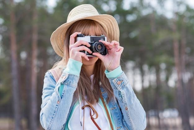 Retrato de una mujer con sombrero tomando foto con cámara vintage