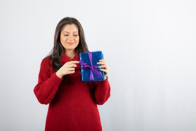 Retrato de una mujer sonriente abriendo una caja de regalo de navidad con cinta morada.
