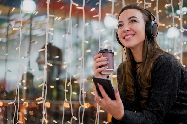 Retrato de mujer sonriente con auriculares con taza y teléfono cerca de luces de navidad