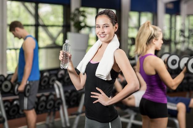Retrato de la mujer sonriente bonita con la botella de agua en el gimnasio