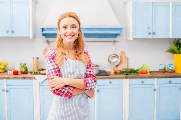 Retrato de una mujer sonriente con los brazos cruzados mirando a la cámara