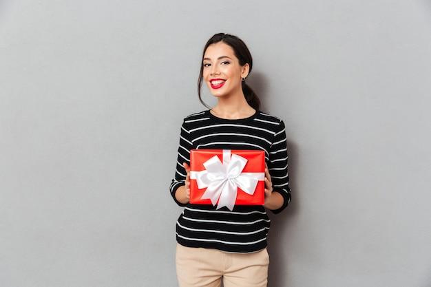 Retrato de una mujer sonriente con caja de regalo