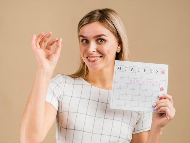 Retrato de mujer sonriente con calendario de menstruación