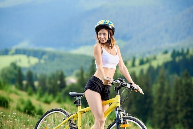 Retrato de mujer sonriente ciclista montando en bicicleta amarilla en las montañas, con casco. montañas, bosques en el fondo borroso. actividad deportiva al aire libre, concepto de estilo de vida. copia espacio