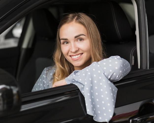 Retrato de mujer sonriente en coche moderno