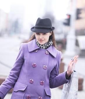 Retrato de mujer sonriente con compras en el fondo de la ciudad borrosa