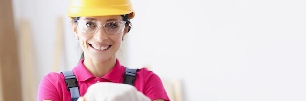 Retrato de mujer sonriente constructor en casco amarillo