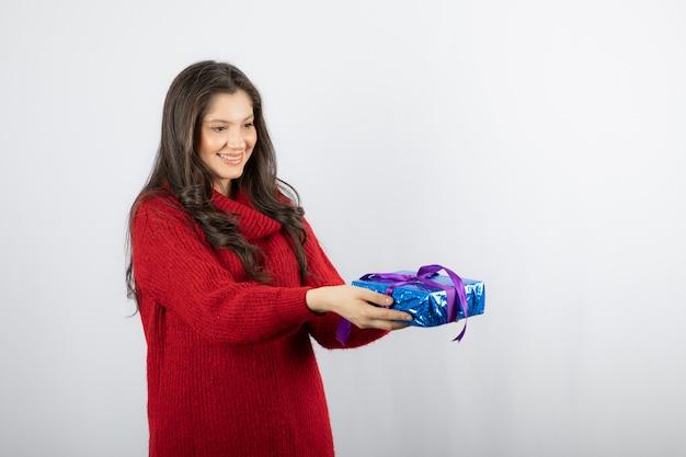 Retrato de una mujer sonriente dando una caja de regalo de navidad con cinta morada.