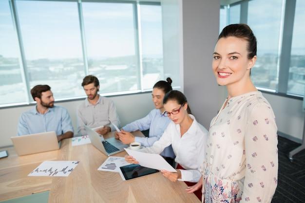 Retrato de mujer sonriente ejecutivo de negocios de pie en la sala de conferencias