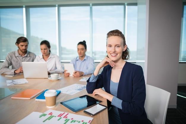 Retrato de mujer sonriente ejecutivo de negocios sentado en la sala de conferencias