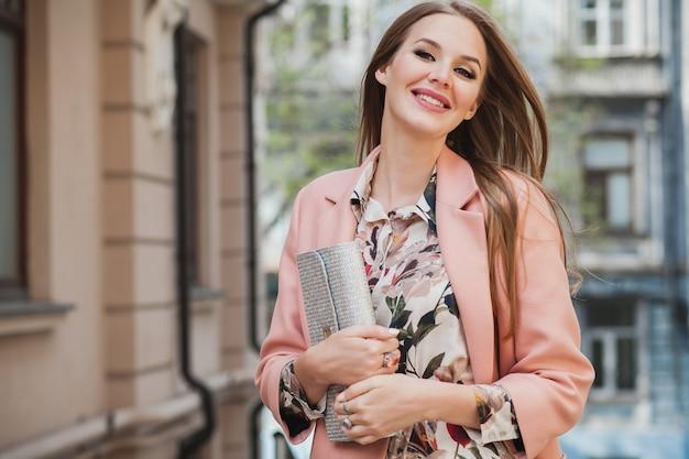 Retrato de mujer sonriente elegante atractiva caminando calle de la ciudad en abrigo rosa y vestido floral