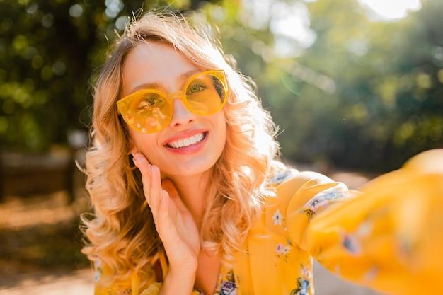 Retrato de mujer sonriente elegante rubia hermosa en blusa amarilla con gafas de sol haciendo foto selfie