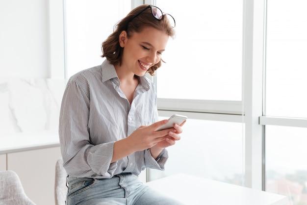 Retrato de una mujer sonriente enviando mensajes de texto en el teléfono móvil