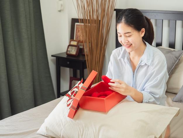 Retrato de una mujer sonriente feliz abrir una caja de regalo en la cama