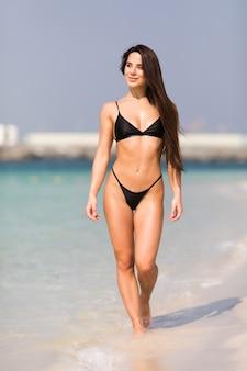 Retrato de mujer sonriente feliz en bikini negro caminando por la playa