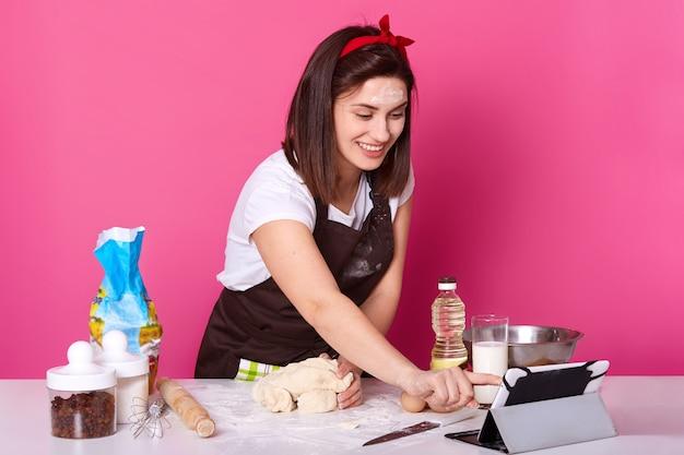 El retrato de la mujer sonriente feliz mira la tableta mientras amasa la masa, prepara pasteles caseros, hornea el pastel de pascua y el bollo cruzado caliente, tiene videollamada con un amigo, está de buen humor y se viste casualmente.