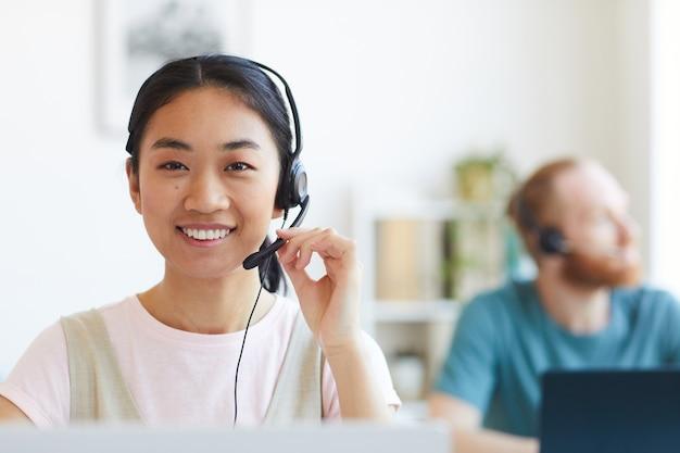 Retrato de mujer sonriente feliz operador telefónico de soporte al cliente en el lugar de trabajo