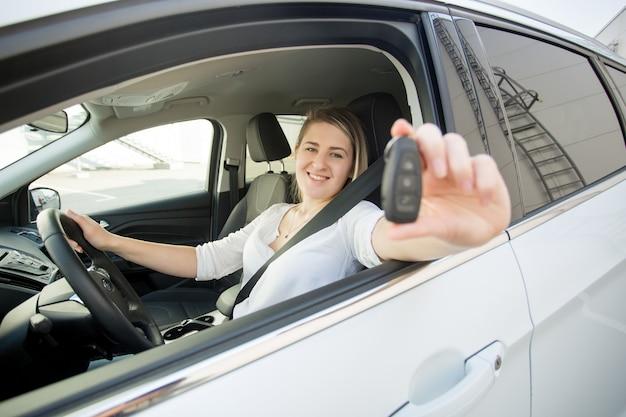 Retrato de mujer sonriente feliz sentado en el coche y mostrando las llaves del coche