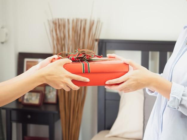 El retrato de una mujer sonriente feliz toma una caja de regalo