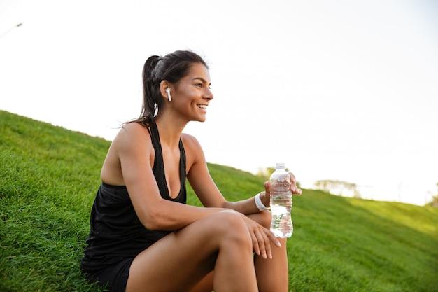 Retrato de una mujer sonriente de fitness en auriculares