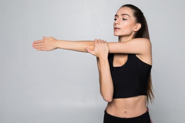 Retrato de una mujer sonriente de fitness estirando sus manos sobre la pared blanca