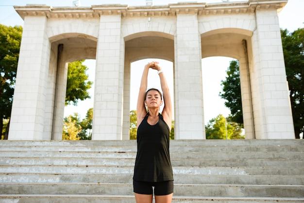 Retrato de una mujer sonriente de fitness estirando sus manos