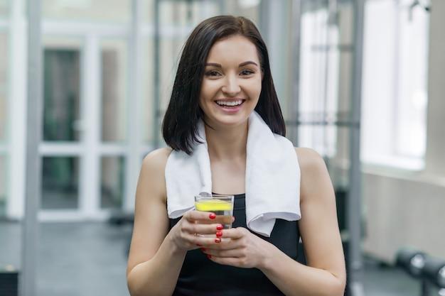 Retrato de mujer sonriente fitness con vaso de agua con limón