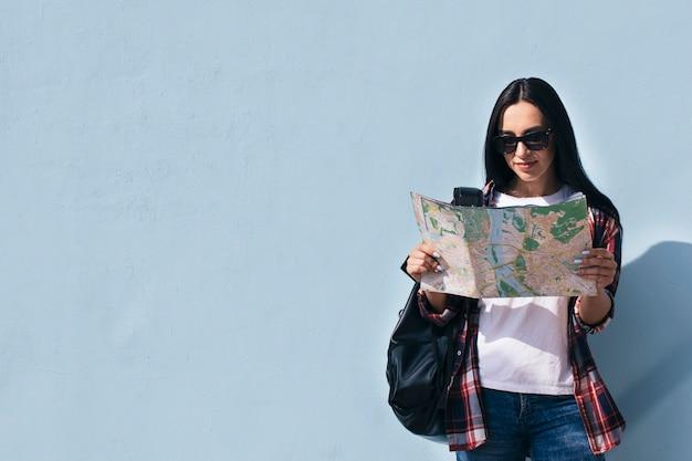Retrato de mujer sonriente con gafas de sol leyendo el mapa y de pie cerca de la pared azul