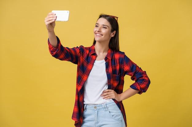 Retrato de una mujer sonriente haciendo selfie foto en smartphone