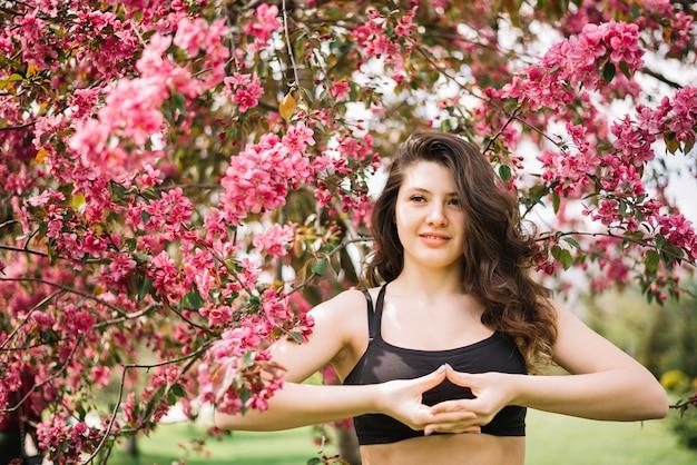 Retrato de mujer sonriente haciendo yoga mudra gesto en el parque