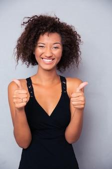 Retrato de una mujer sonriente mostrando el pulgar hacia arriba sobre la pared gris