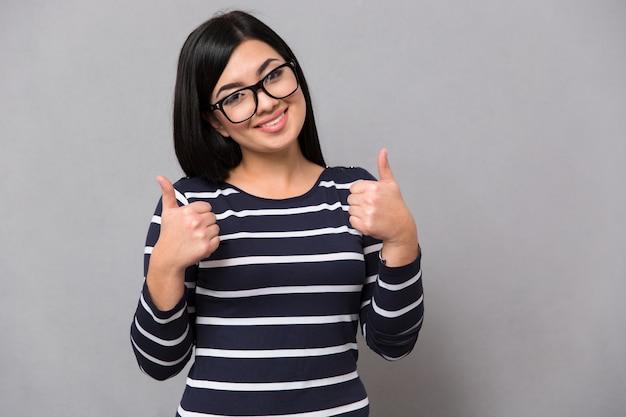 Retrato de una mujer sonriente mostrando los pulgares hacia arriba sobre la pared gris