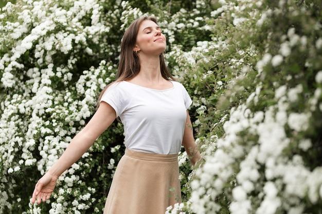 Retrato mujer sonriente oliendo flores