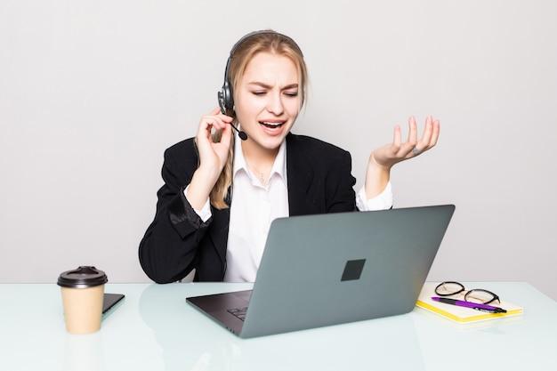 Retrato de mujer sonriente con operador de línea de ayuda portátil con auriculares en la oficina