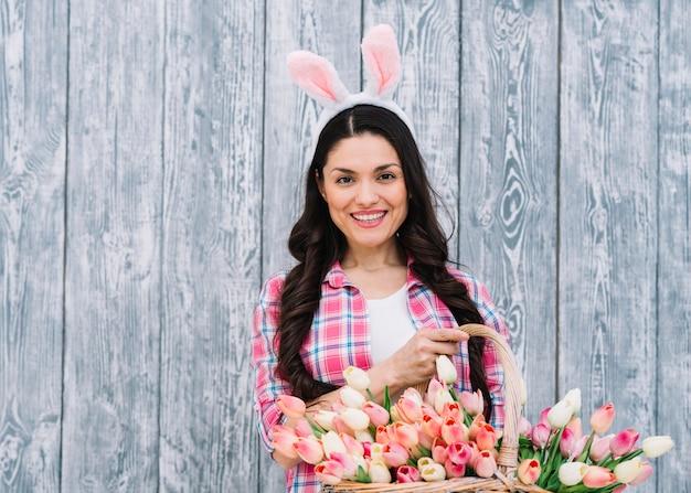 Retrato de una mujer sonriente con orejas de conejo en la cabeza con una canasta de tulipanes sobre fondo de madera