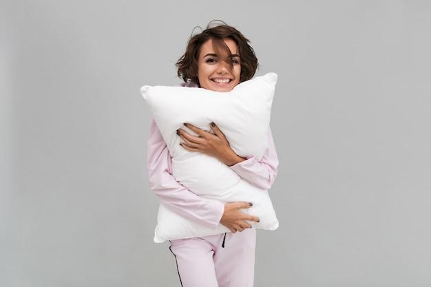 Retrato de una mujer sonriente en pijama sosteniendo una almohada
