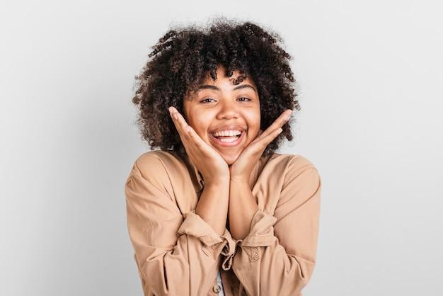 Retrato de mujer sonriente poniendo la mano alrededor de su cara