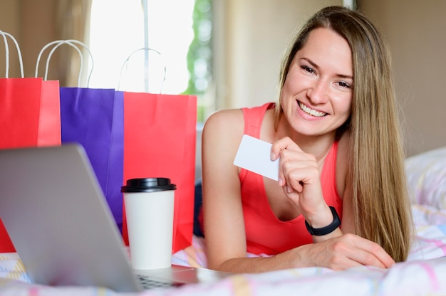 Retrato de mujer sonriente posando con bolsas de compras